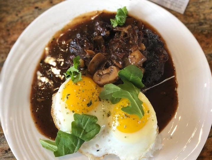 meat served in a brown sauce with mushrooms and egg side