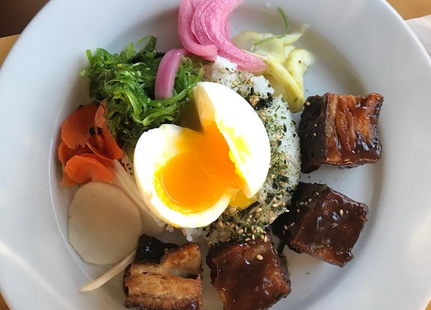 hardboiled egg over rice with side of meat and vegetables