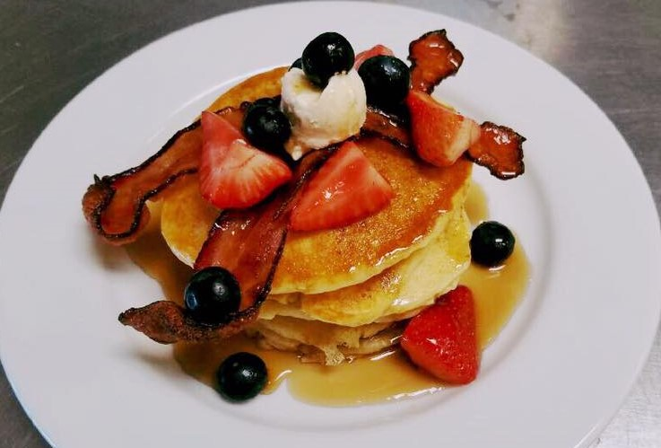 pancakes with syrup, bacon and fruit