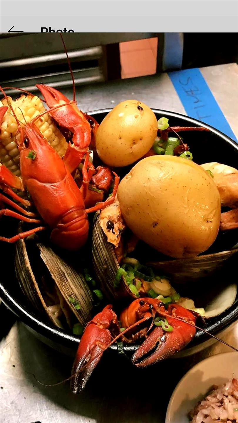 a bowl with lobsters, potatoes, corn and clams