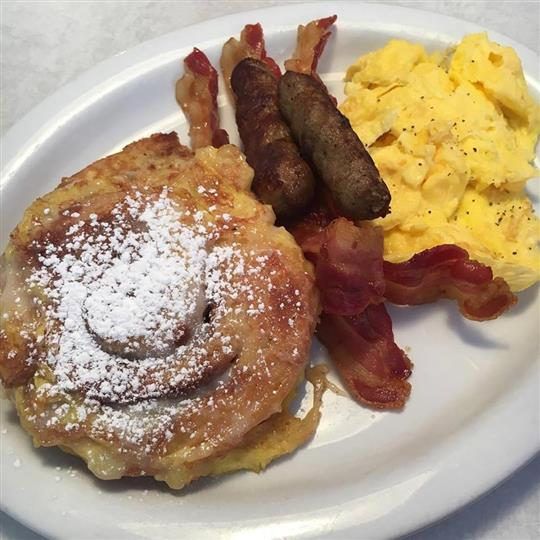 challah bread French Toast served with scrambled eggs and two strips of bacon  and two sausage links