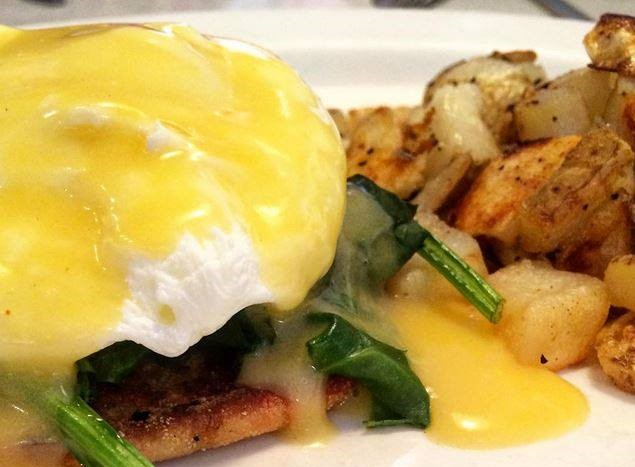 Eggs benedict with spinach and hollandaise sauce on an english muffin and a side of fried potatoes.