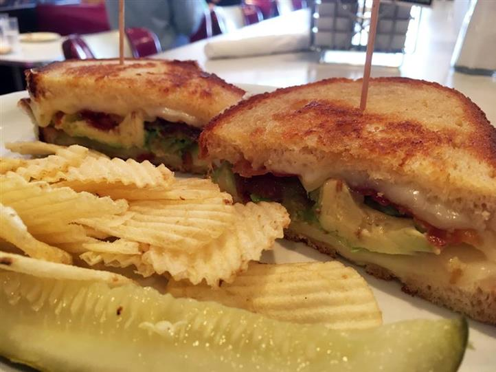 toasted sandwich with bacon, tomato, avocado, melted cheese  and a side of potato chips and a pickle spear