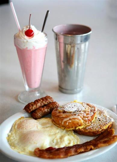 two over medium eggs, two breakfast sausages, two slices of bacon and two Challah bread French Toast topped with powdered sugar with a pink milkshake topped with whipped cream and a cherry on top