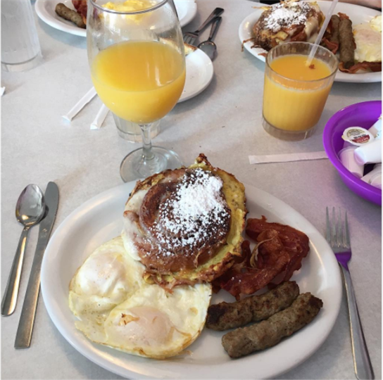 Challah bread French Toast served with two eggs any style and two strips of bacon or two sausage links