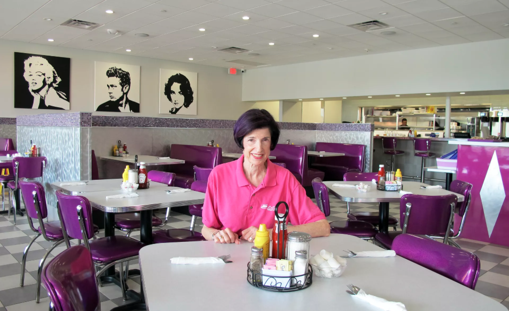Woman with purple hair and a hot pink collared shirt smiling inside LuLu B's Diner at a table