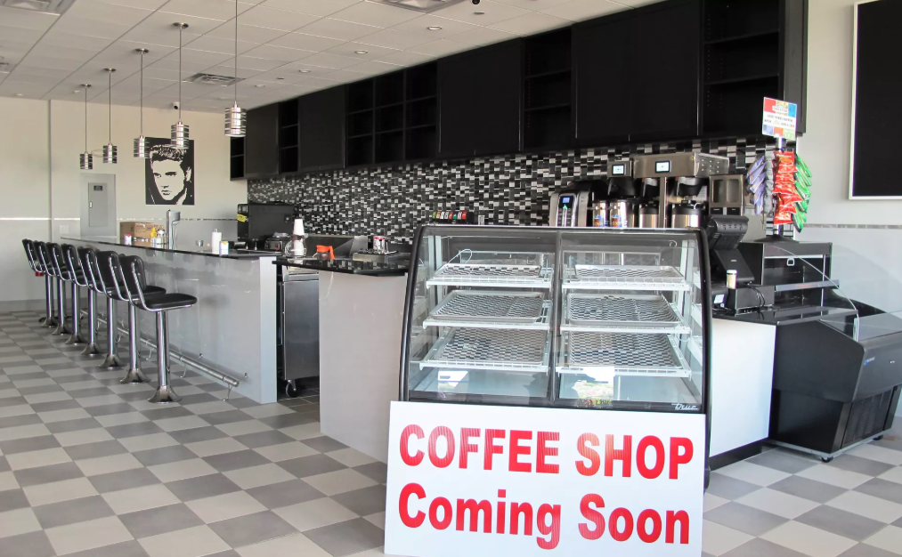 "Picture of a coffee bar with empty bar stools lined up at the counter and a sign saying "" Coffee shop coming soon"" infront of an empty case"