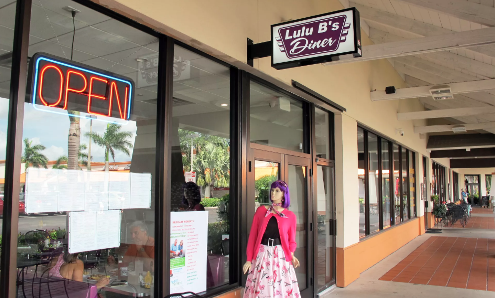 Picture of the front of LuLu B's Diner with a mannequin infront and a neon OPEN sign in the window