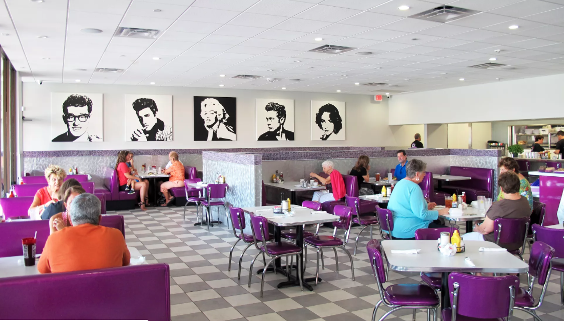 Black and white pop- art wall art of famous figures including marilyn Monroe and evis presley above booths  and tableswith purple seating filled with people and checkered floors