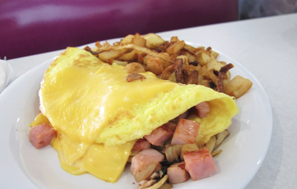 Omelette stuffed with cheese, diced ham and onions with a side of home fries