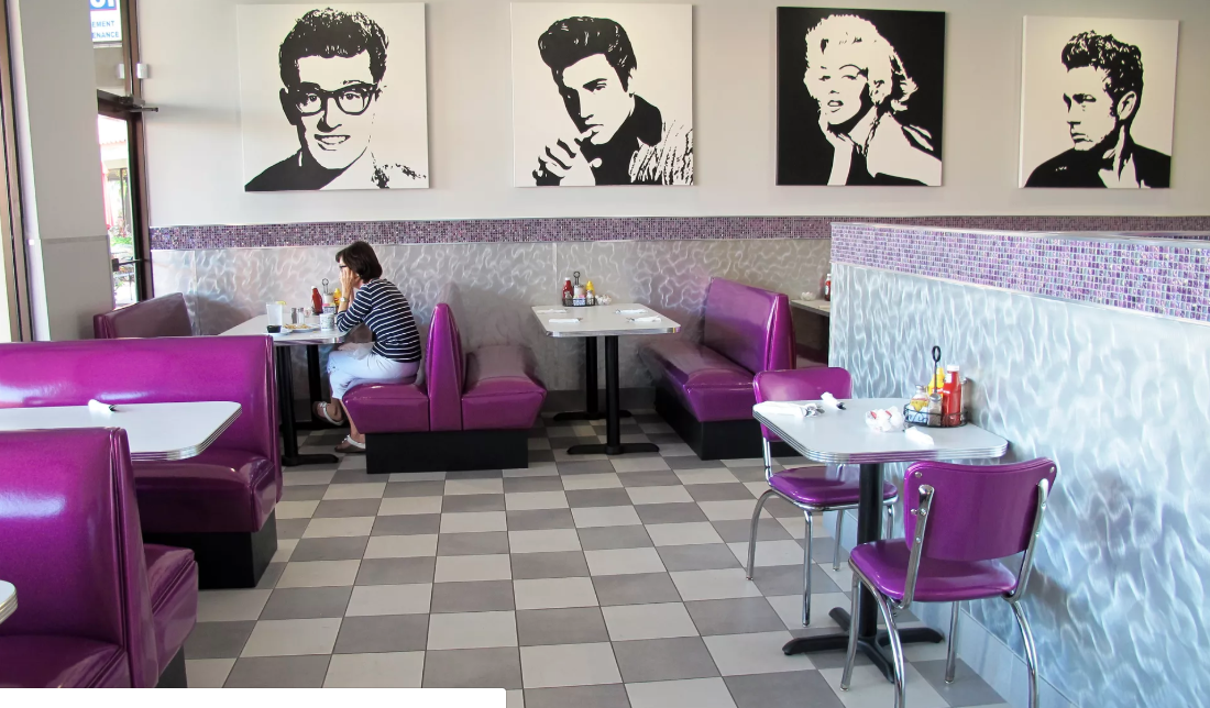 Black and white pop- art wall art of famous figures including marilyn Monroe and evis presley above empty booths with purple seating and checkered floors