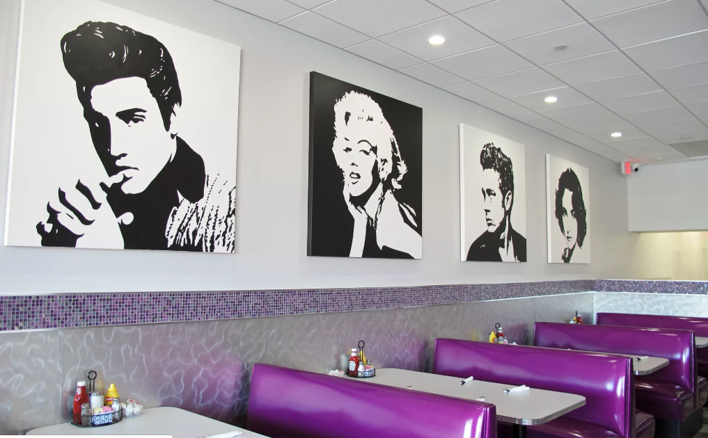Black and white pop- art wall art of famous figures including marilyn Monroe and evis presley above empty booths with purple seating