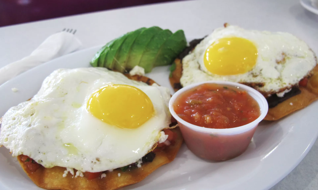Two crispy corn tortillas layered with refried black beans, Pico de Gallo, queso fresco and topped with 2 sunny side up eggs and a side of  salsa