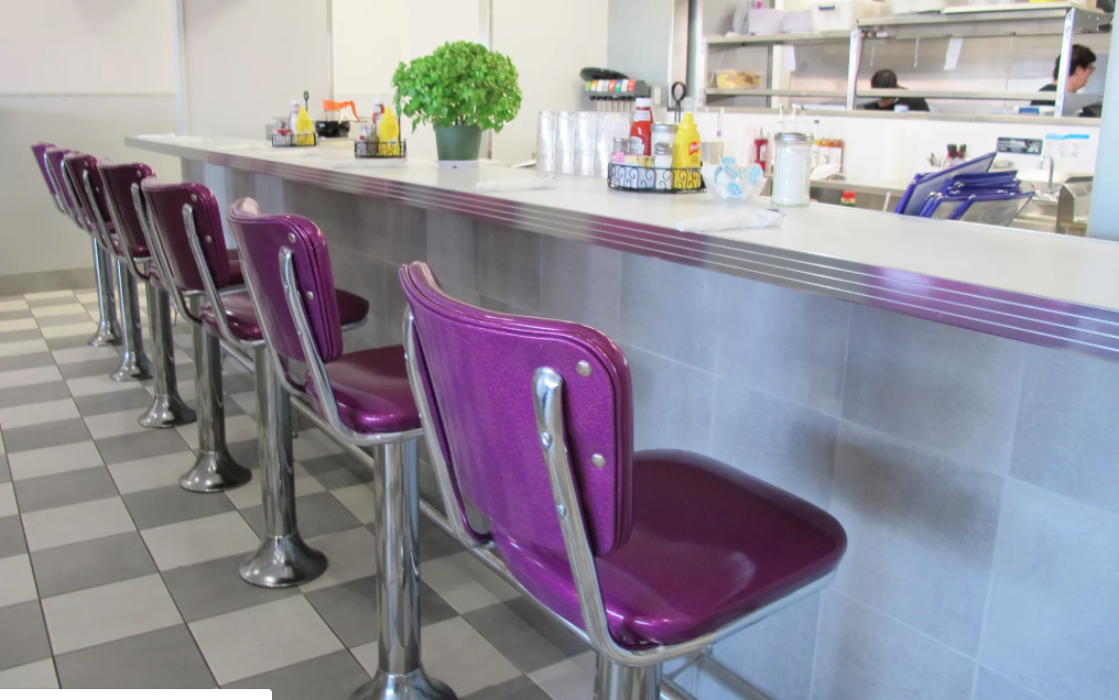 Empty Purple sparkly bar stools lined up at counter