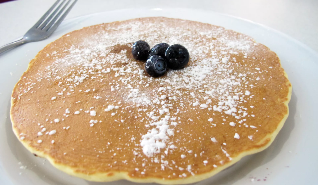 pancakes dusted with powdered sugar and blueberries in the center