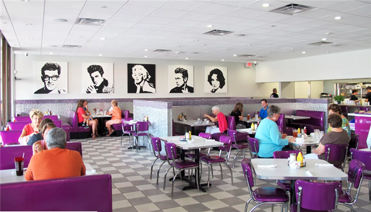 inside of lulu B's restuarant with multiple booths and tables and 5 big pictures on the wall of famous people