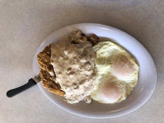 fried chicken topped with a white sauce with 2 eggs on the side