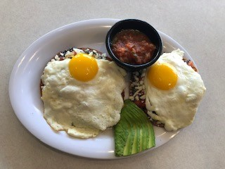 two eggs with an avocado and salsa on the side