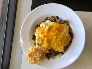 Three eggs scrambled with sausage, bacon, peppers, onion and mushrooms; topped with melted cheddar and sausage gravy. Served over home fries with a biscuit