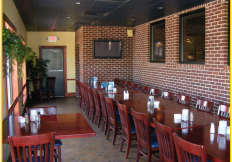 Interior of restaurant with tables and chairs and a brick wall