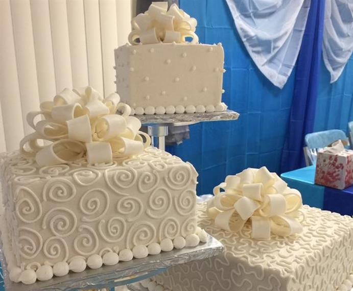 Image of white wedding cakes with piped decorations on cake stands