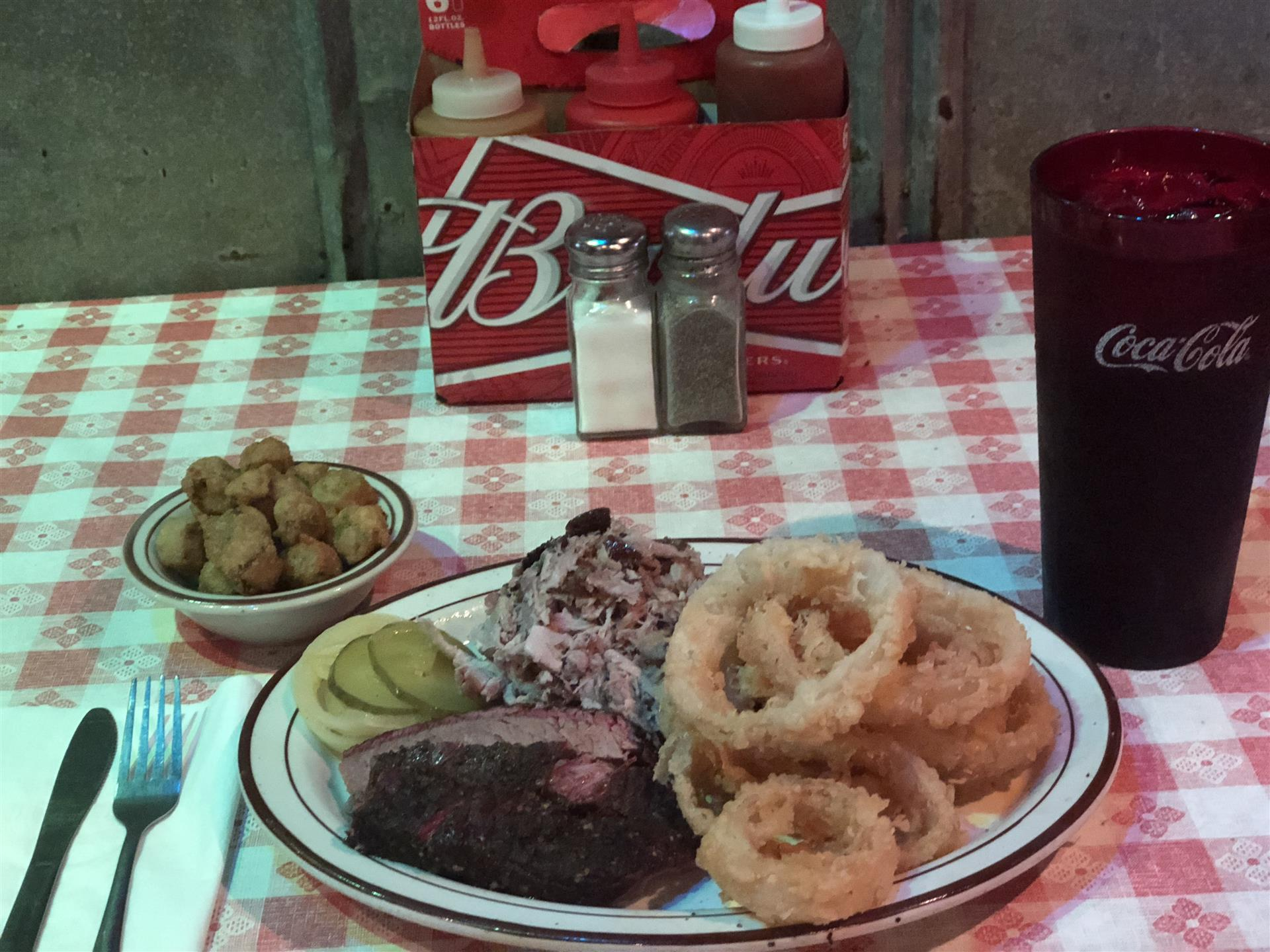 Brisket and onion rings on a plate next to a cup of soda and tater tots