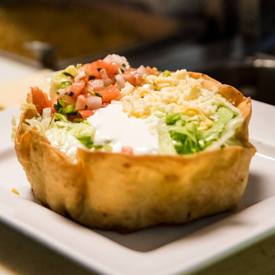 Fresh taco salad bowl with lettuce, pico de gallo, sour cream and cheese