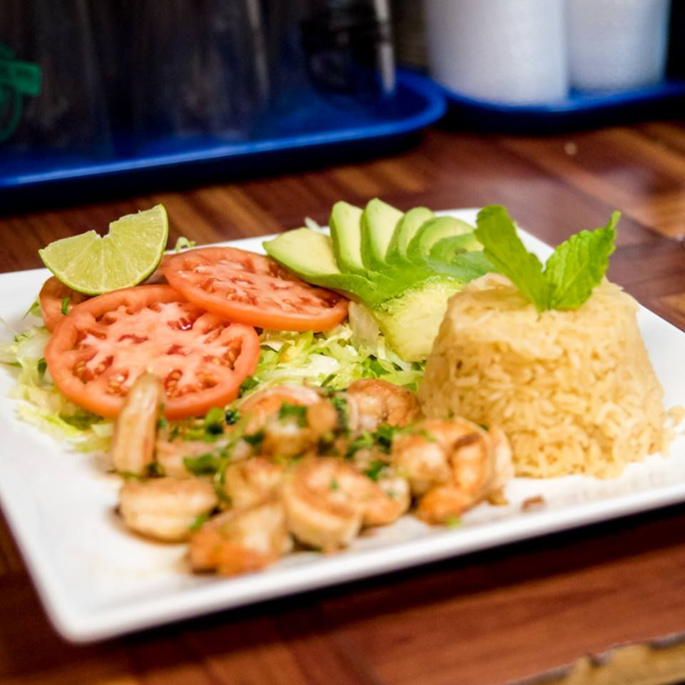 Grilled shrimp dish with side of yellow rice, sliced avocados, tomates and lime