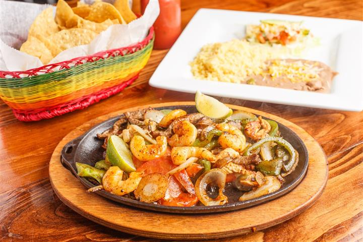 El Centro Fajita, Grilled steak, chicken, and sautéed shrimp with sautéed onions, tomatoes, and bell peppers. Served with rice, beans, avocado slices, fresh lettuce, and pico de gallo.