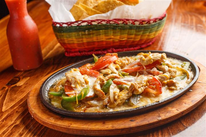 Chicken on a skillet with sautéed onions, tomatoes, and bell peppers. Served with rice, beans, avocado slices, fresh lettuce, and pico de gallo.