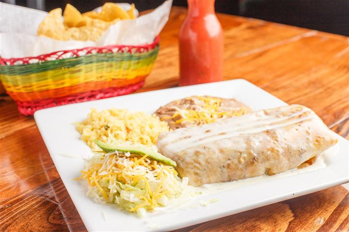Burrito on a plate with rice and refried beans on the side, also served with shredded lettuce and shredded cheese with a slice of avocado.