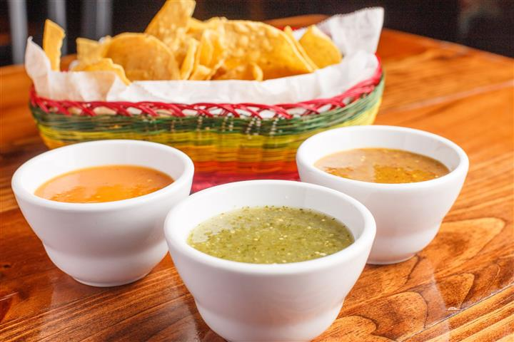 Three small cups of mild verde salsa, medium tomatillo salsa, and hot habanero salsa with a basket of chips in the background.
