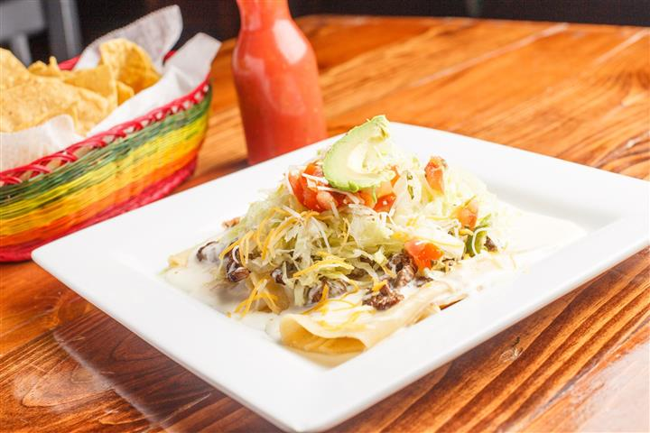 Enchilada Plate,Three enchiladas with your choice of meat topped with green sauce and queso. Served with lettuce, pico de gallo, shredded cheese, avocado slices, rice, and beans