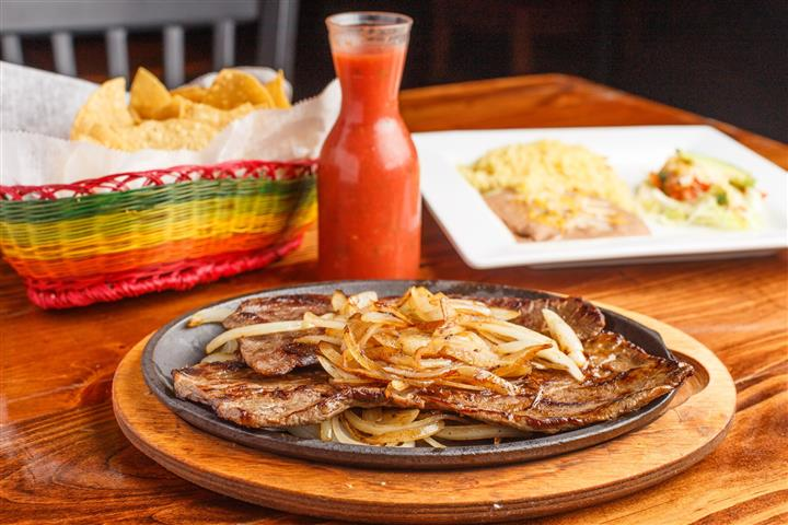 Skillet with grilled steak and onions served with a side of rice and refried beans with a glass of salsa.