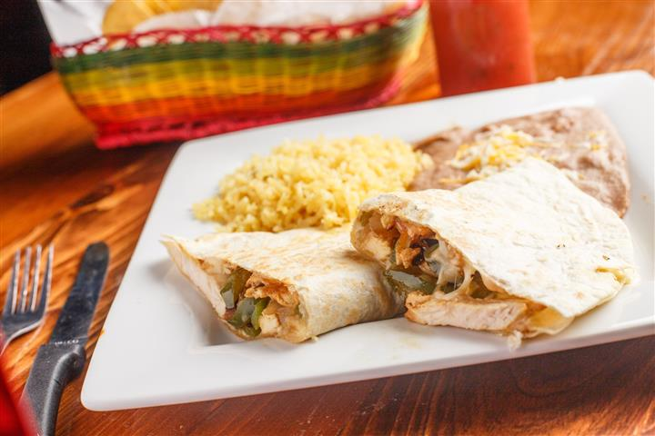 Burrito filled with grilled chicken and bell peppers, served with a side of rice and refried beans.