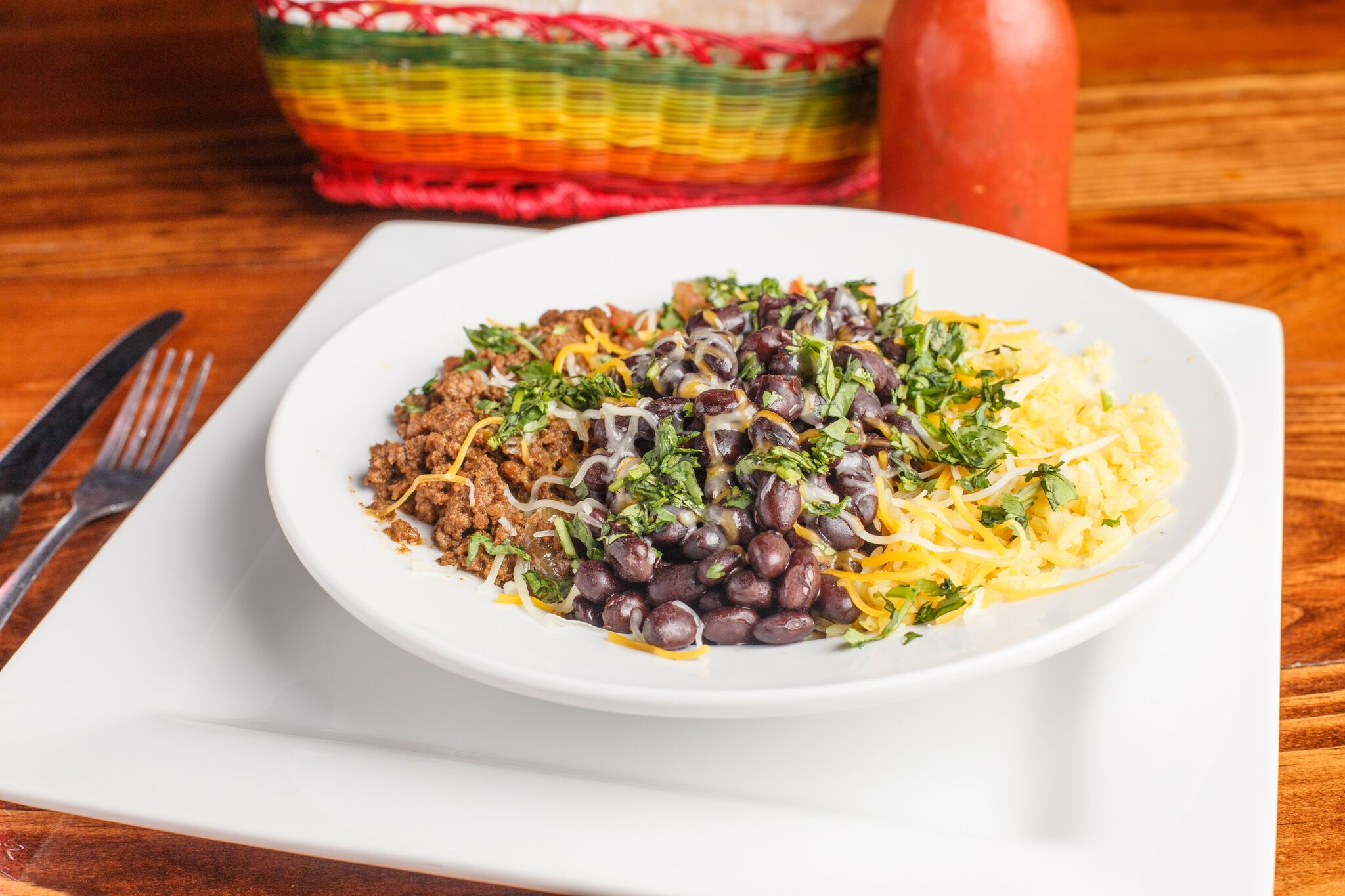 plate with ground beef, black beans and yellow rice sprinkled with cilantro and shredded cheese.