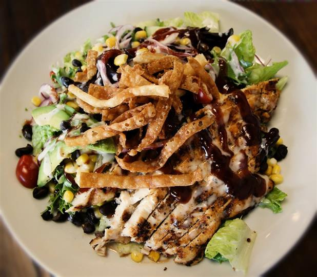 top view of the BBQ Chicken Salad which includes Iceberg Romaine, Mix Green, Avocado, Corn, Black Bean, Cucumber, Tomatoes, Onions, Wonton Strips, Barbeque Ranch Dressing