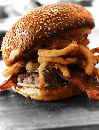 burger with applewood bacon and onion rings on a toasted sesame bun