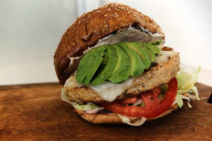 turkey burger with avocado, lettuce and tomato on a toasted sesame bun