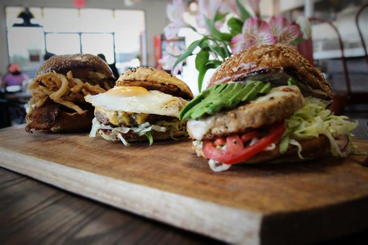 Three burgers on a cutting board, each with different toppings and different buns,