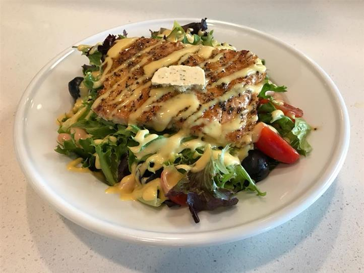 Mixed greens topped with salad topped with salmon, tomato and black olives with dijon mustard dressing.