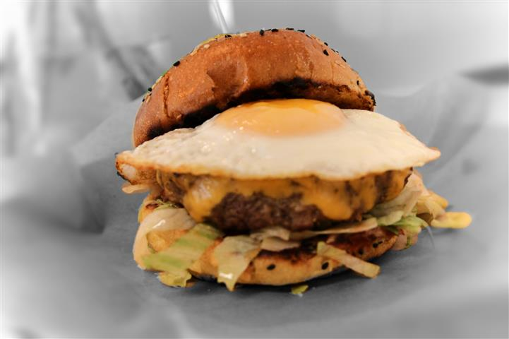 Burger with american or cheddar cheese, a fried egg and lettuce on a toasted sesame bun.