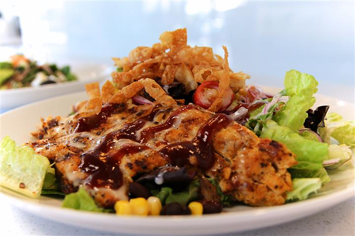 closeup of the BBQ Chicken Salad which includes Iceberg Romaine, Mix Green, Avocado, Corn, Black Bean, Cucumber, Tomatoes, Onions, Wonton Strips, Barbeque Ranch Dressing