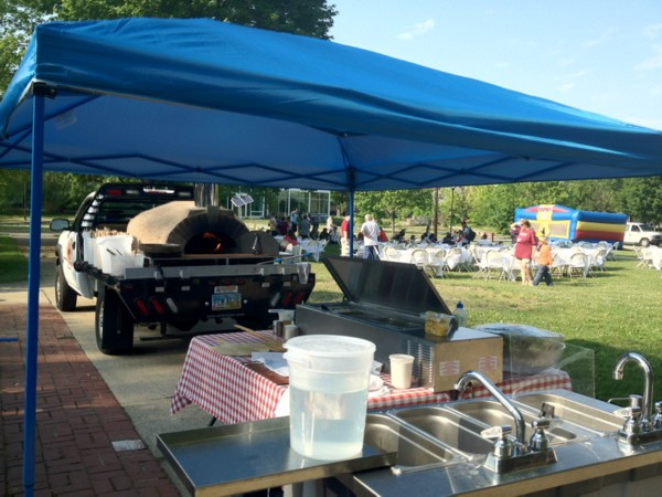 Lorenzo's Pizzeria catering setup with wood-burning brick oven on a truck bed