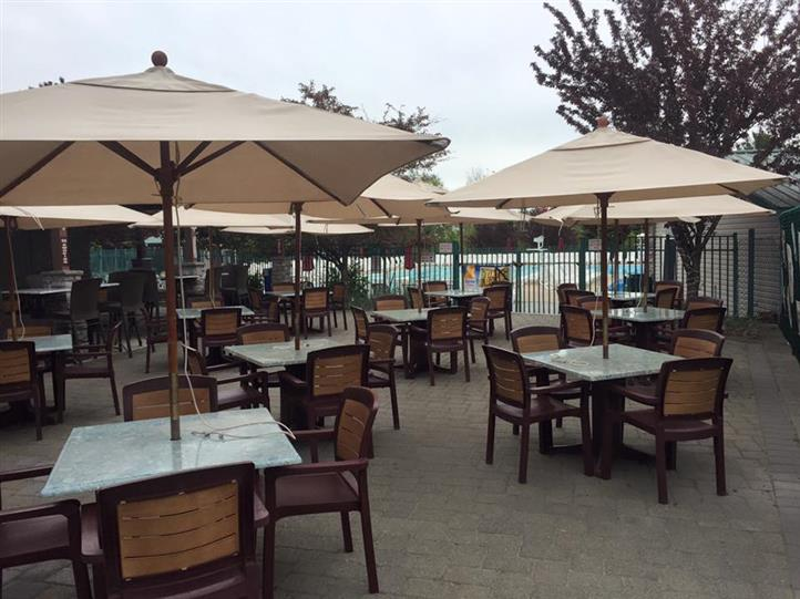 outdoor seating area with 11 tables and four chairs at each table with a beige umbrella at each table