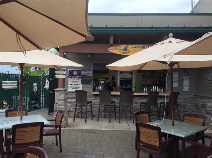 outdoor seating area of two tables with four chairs at each table, two umbrellas and a bar with five stools at it