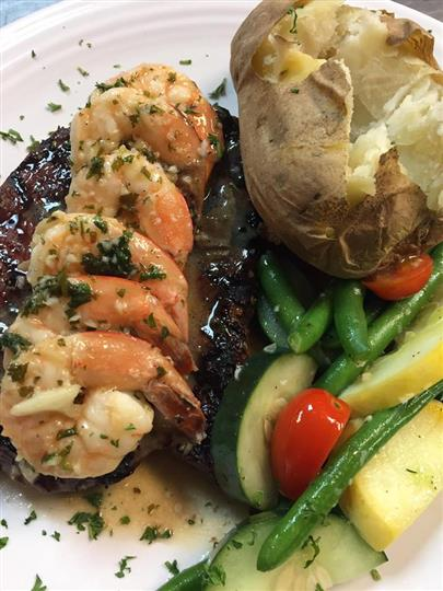 a steak with six shrimp and a side of baked potato with zucchini, tomato and green beans