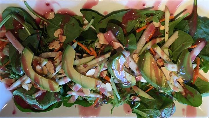 a salad with spinach, avocado, cheese, carrots, almonds, and a pink vinaigrette