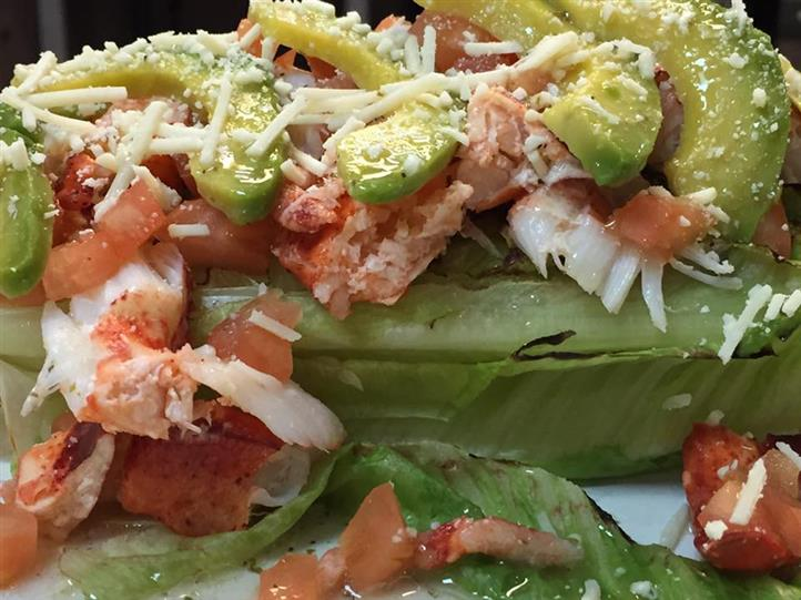 a bed of lettuce with lobster meat, tomato, cheese, and avocado on top