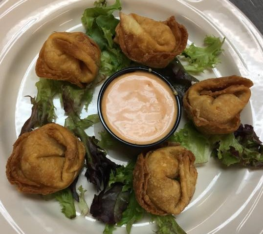 five fried wontons on a bed of lettuce with a side of orange dipping sauce